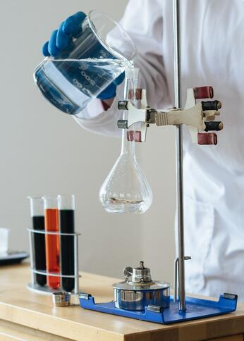 crop-chemist-pouring-clear-liquid-into-fragile-glassware-in-3825379